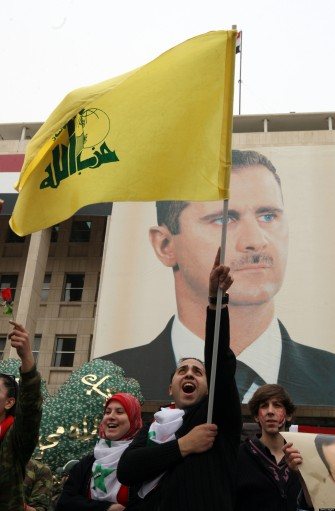 Syrian demonstrators hold up a Lebanese